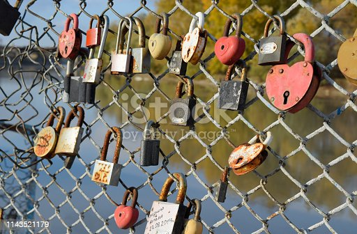 872969580 istock photo Love locks hung by newlyweds and lovers on the fence near the ri 1143521179