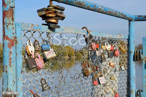 istock Love locks hung by newlyweds and lovers on the fence near the river. A symbol of strong relationships and eternal love 872969552