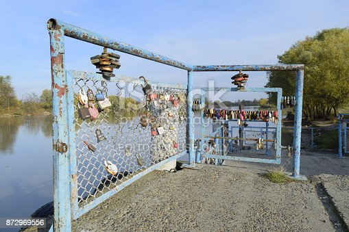 istock Love locks hung by newlyweds and lovers on the fence near the river. A symbol of strong relationships and eternal love 872969556