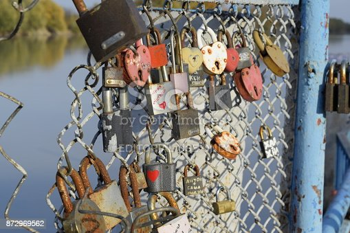 istock Love locks hung by newlyweds and lovers on the fence near the river. A symbol of strong relationships and eternal love 872969562