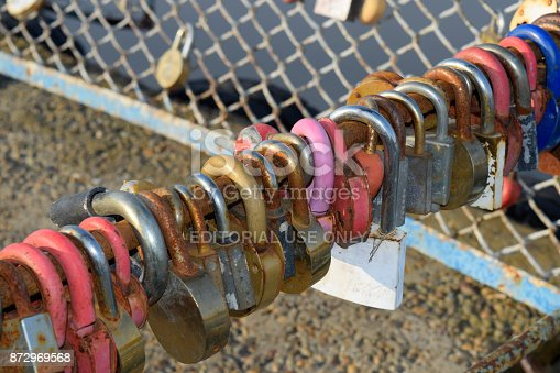 istock Love locks hung by newlyweds and lovers on the fence near the river. A symbol of strong relationships and eternal love 872969568