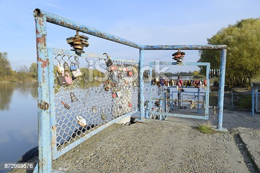 istock Love locks hung by newlyweds and lovers on the fence near the river. A symbol of strong relationships and eternal love 872969576