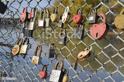 872969580 istock photo Love locks hung by newlyweds and lovers on the fence near the river. A symbol of strong relationships and eternal love 872969580