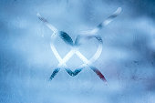 Love loneliness winter concept. Crossed heart handwritten symbol on the blue glass window with frozen patterns