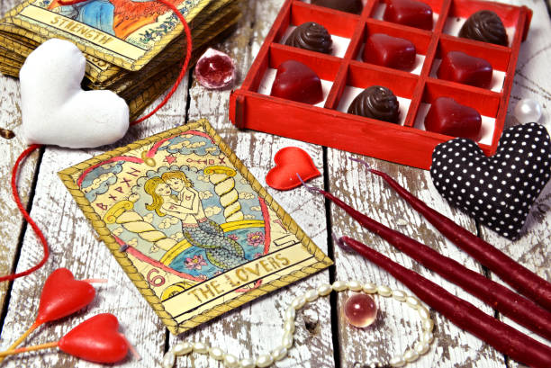 Love magic ritual with red candles, tarot card Lovers, heart symbols and chocolate candies. stock photo