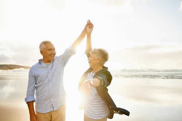 Love makes the good times even better Shot of a happy senior couple dancing at the beach young at heart stock pictures, royalty-free photos & images