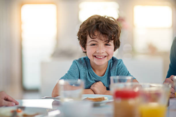 I love me some breakfast Cropped portrait of an adorable little boy eating breakfast while sitting at the dining room table one boy only stock pictures, royalty-free photos & images