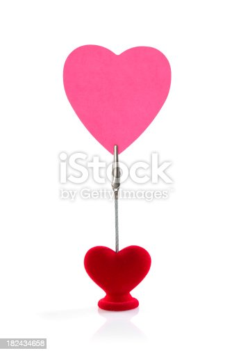 A clip holding blank pink heart shape paper on white background