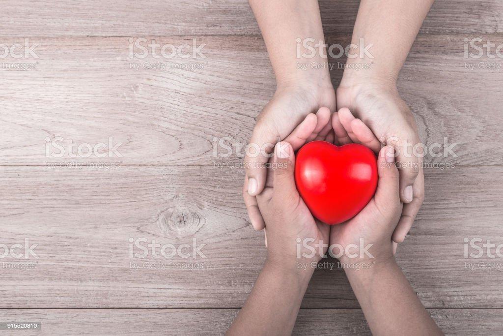 Liebe Mama Konzept: Frau hält ihre kleine Kinder Hände rotes Herz auf braunen Holztisch zu unterstützen. Freiraum für Text Muttertagsfeier. – Foto