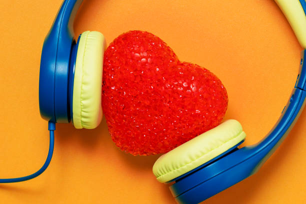Love music (headphones with a red heart on an orange background) stock photo