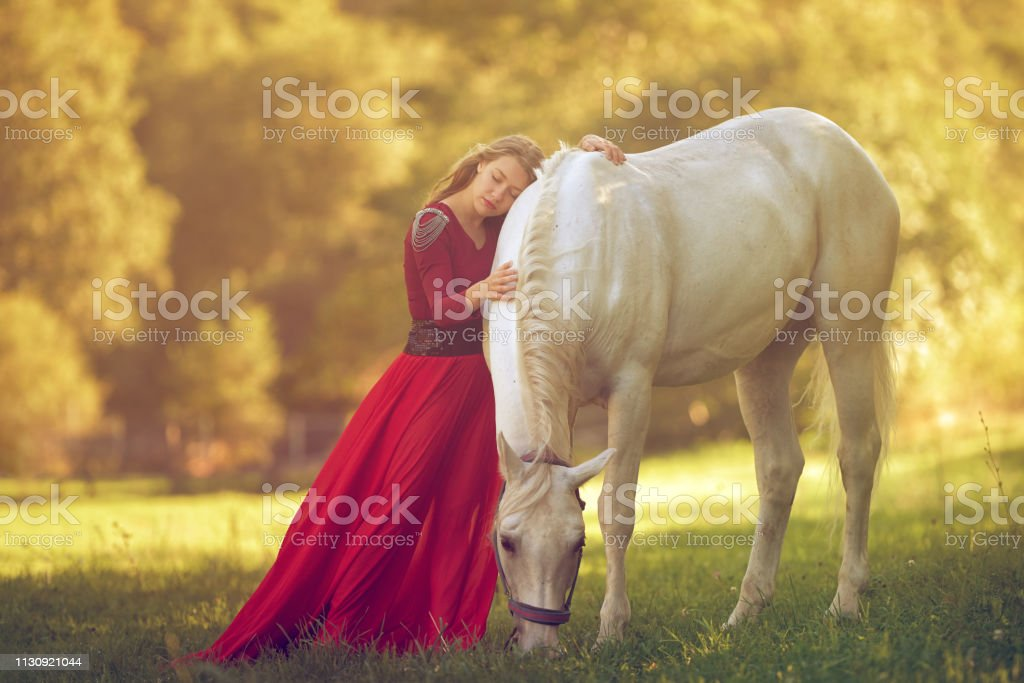 attractive fairy woman in red dress embracing her white horse in...