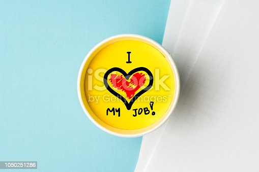 istock I love my job concept. Paper cup wint yellow top and blue background desk with notes. 1050251286