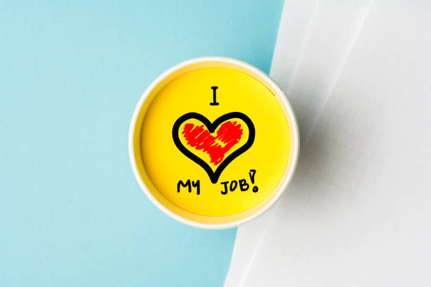 i love my job concept. paper cup wint yellow top and blue background desk with notes. - fidanzamento foto e immagini stock