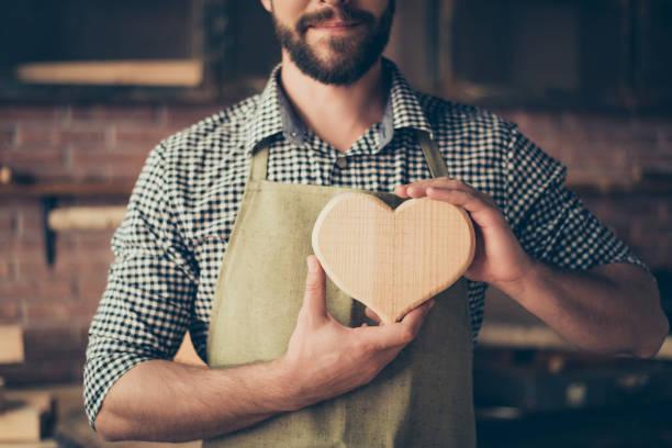 ¡me encanta mi trabajo! recortada de cerca foto de carpintero alegre alegre feliz en el amor, muestra un corazón de madera - carpintero fotografías e imágenes de stock