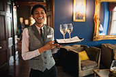 A well-dressed waitress is laughing and enjoying being at work, while she is holding wine glasses to be served to guests.