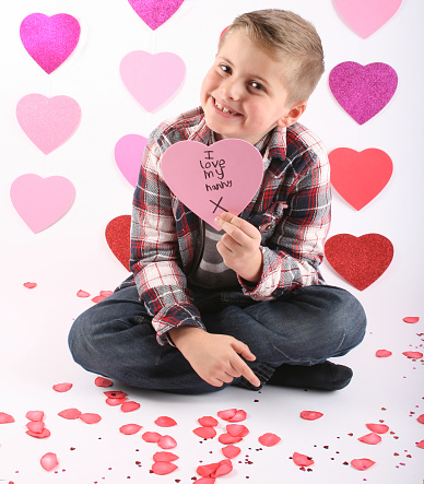 7 year old holding a heart sign saying 'i love my nanny'