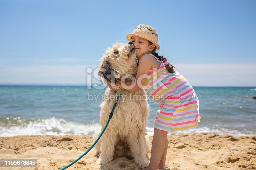 Adorable young girl enjoying family vacation on a summer day at the beach.