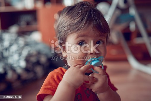 funny baby girl with blue eyes holding pacifier, looking at camera.