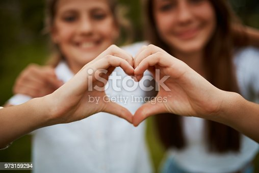Closeup shot of two young sisters' hands making a heart shape