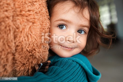 adorable little girl embracing her toy and smiling at camera.