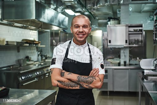 I love my work Cheerful young chef in apron keeping tattooed arms crossed and smiling while standing in a restaurant kitchen. Cooking concept