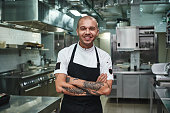 istock I love my work Cheerful young chef in apron keeping tattooed arms crossed and smiling while standing in a restaurant kitchen 1136638047