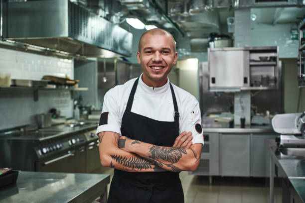 i love my work cheerful young chef in apron keeping tattooed arms crossed and smiling while standing in a restaurant kitchen - cooker happy imagens e fotografias de stock