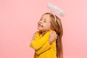 I love myself. Beautiful charming little girl with halo over head embracing herself and smiling from happiness, self-love concept, positive self-esteem. indoor studio shot isolated on pink background