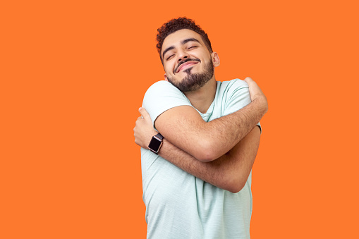 I love myself! Portrait of egoistic brunette embracing himself and smiling form pleasure. indoor studio shot isolated on orange background