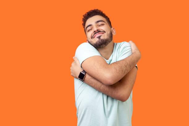 kocham siebie! portret egoistycznej brunetki obejmującej siebie i uśmiechniętą przyjemność formy. kryty studio strzał izolowane na pomarańczowym tle - indywidualność zdjęcia i obrazy z banku zdjęć