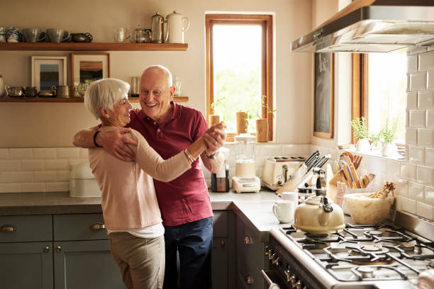 Love never grows old Cropped shot of a senior couple dancing in the kitchen at home dancing stock pictures, royalty-free photos & images