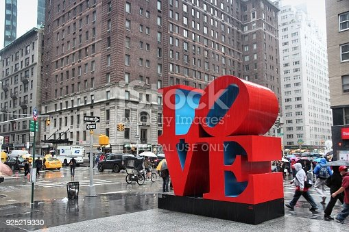 New York: People walk past Love sculpture in rain in New York. The famous monument by Robert Indiana is located on 6th Avenue.