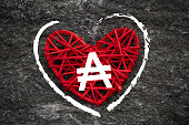 Love of money. Argentina Austral symbol on a red heart