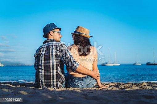 Young Caucasian heterosexual couple enjoying on beach together.