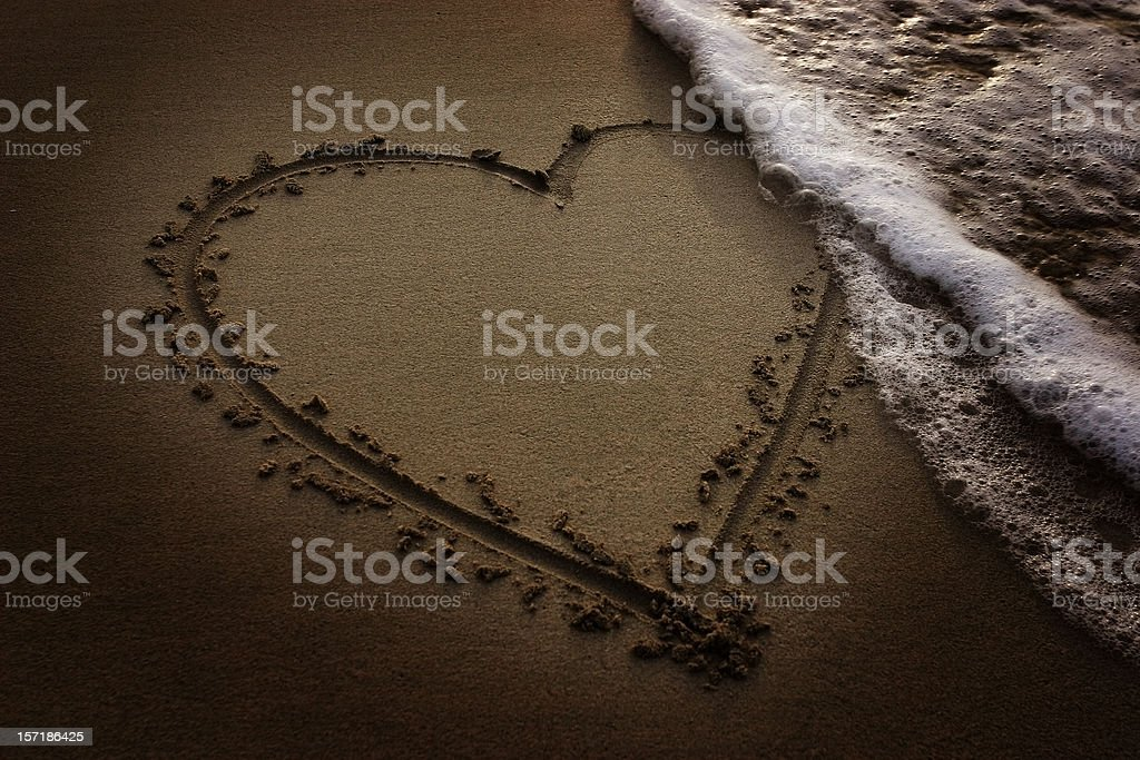 Love on sand Heart drawn on sand, being washed away by waves. Affectionate Stock Photo
