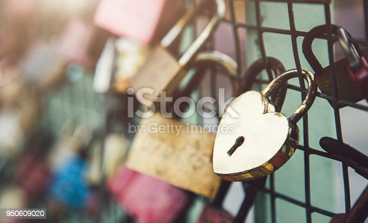 Close up shot of a heart shaped padlock of love locked on a railing of a bridge. Shot in Hamburg, Germany