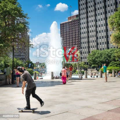Philadelphia, United States - July 5, 2013: Skater passes by The Love Sculpture by the pop artist Robert Indiana, that was placed in Philadelphia's