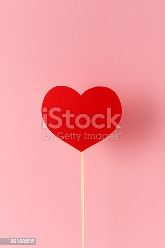 Red heart shape attached to a wood stick before a warm pink background.