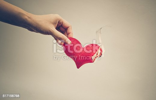 Female hand giving a heart on fire / Dangerous love