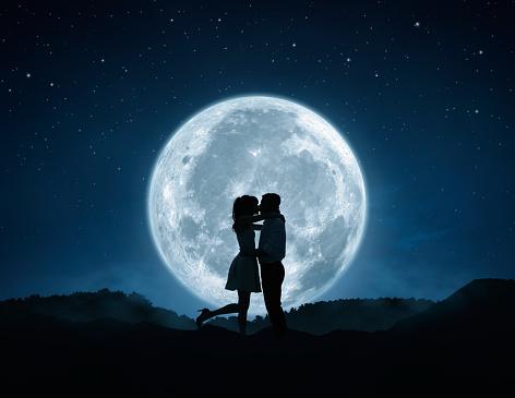 Silhouette of loving couple kissing against the full moon