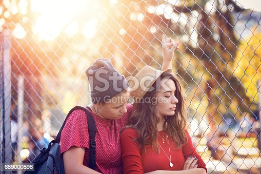 Young frowning woman turning back to her girlfriend