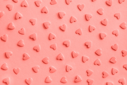 Love romantic pattern. Pink confectionery hearts sprinkles on pink, background, texture Coral toned