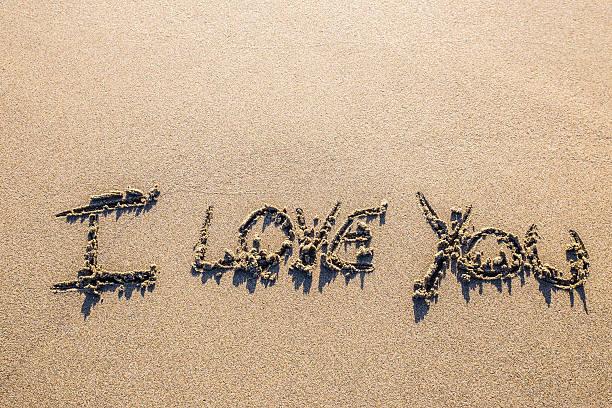love sculpted in the sand - herz zitate stock-fotos und bilder