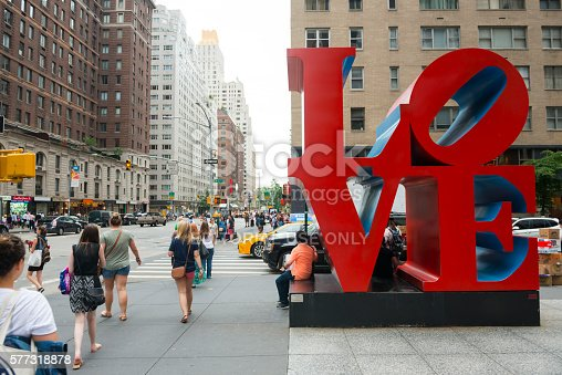 New York City, USA - July 13, 2016: Pedestrians walk past the LOVE sculpture, located at the corner of Sixth Avenue and W 55th Street, in Manhattan, New York City. LOVE is an iconic Pop Art image by American artist Robert Indiana.