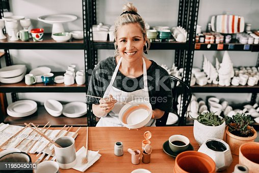 Cropped portrait of an attractive mature woman sitting alone and painting a pottery bowl in her workshop