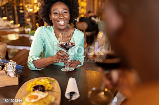 Close up of cheerful African American couple toasting with red wine, celebrating anniversary