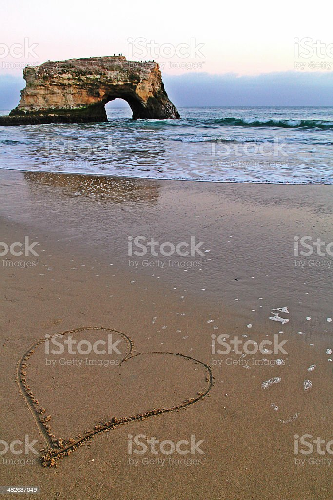 Love Sign Carved on Beach Sand stock photo