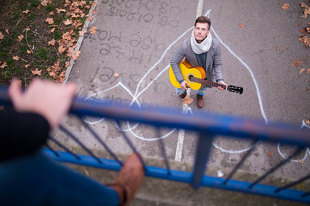 Love Song Guy playing a guitar from under the bridge serenading stock pictures, royalty-free photos & images