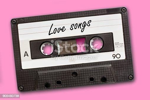 istock Love songs written on vintage audio cassette tape, pink background 905460738