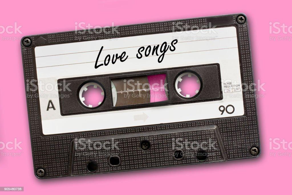 Love songs written on vintage audio cassette tape, pink background stock photo